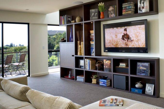 Еще один интересный вариант - установить телевизор среди навесных полок
